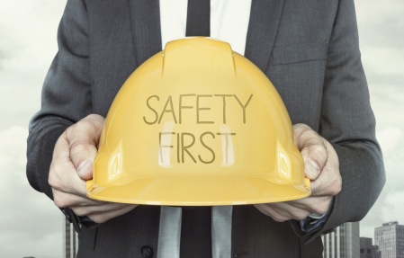 Safety first text on helmet what businessman is holding on cityscape background